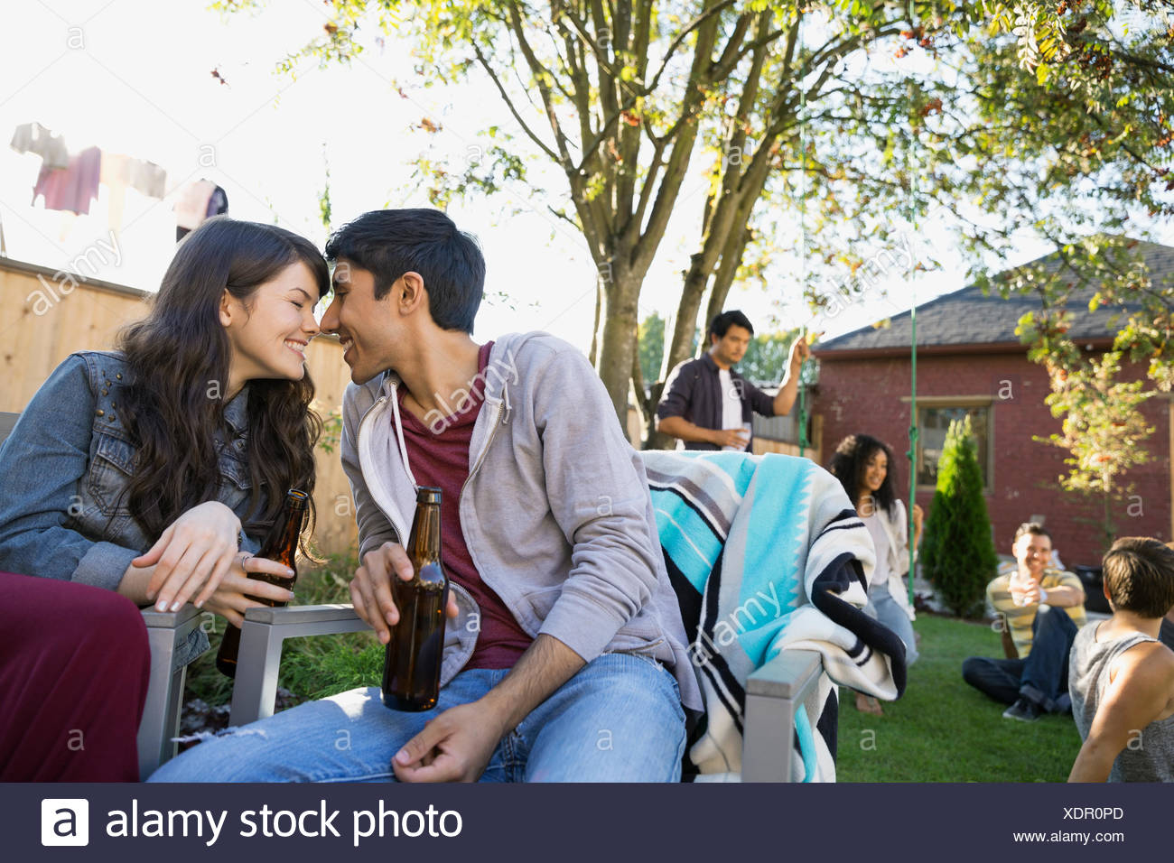 Couple rubbing noses at backyard barbecue - Stock Image