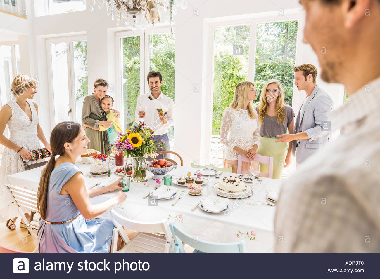 Family chatting around party table  in dining room - Stock Image