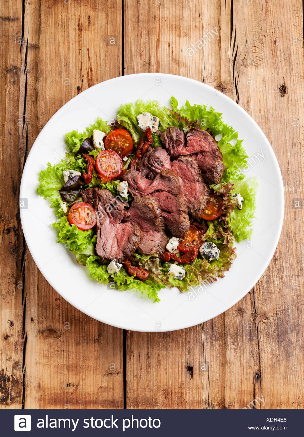 Salad leaves with sliced roast beef and sun-dried cherry tomatoes on wooden background - Stock Image