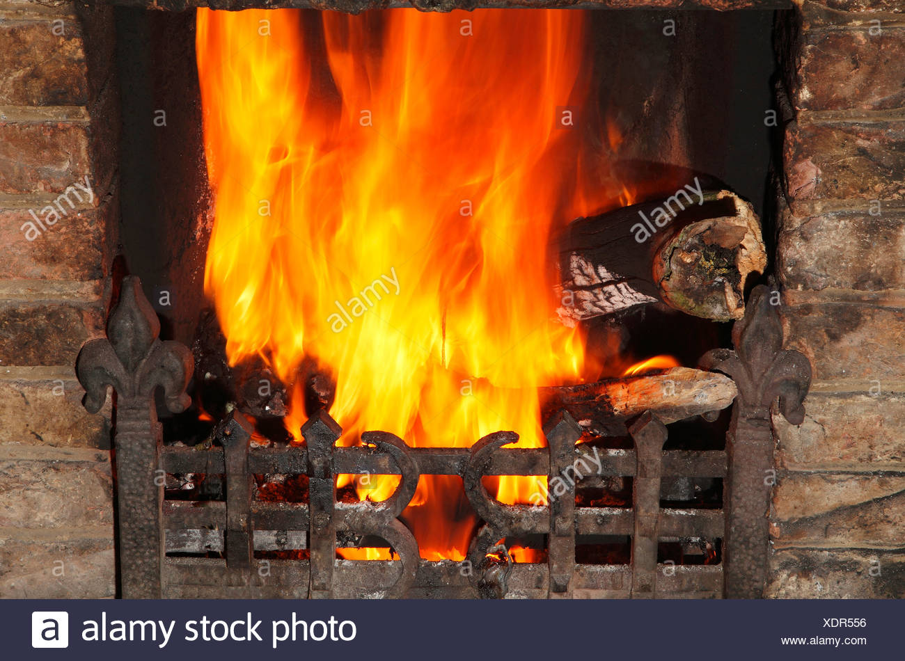 Fire in domestic hearth, heat flame flames heating fireside warmth fires grate burning wood coal home fires - Stock Image