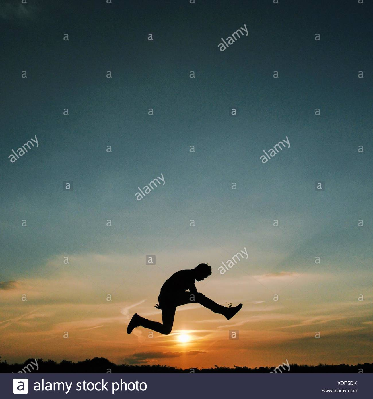 Silhouette of man jumping over sun - Stock Image