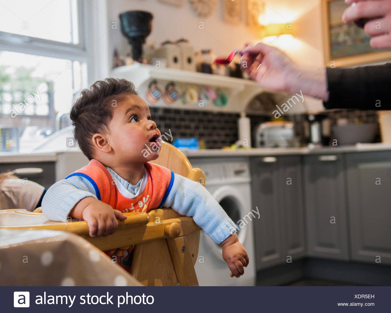 Baby boy in highchair being fed - Stock Image