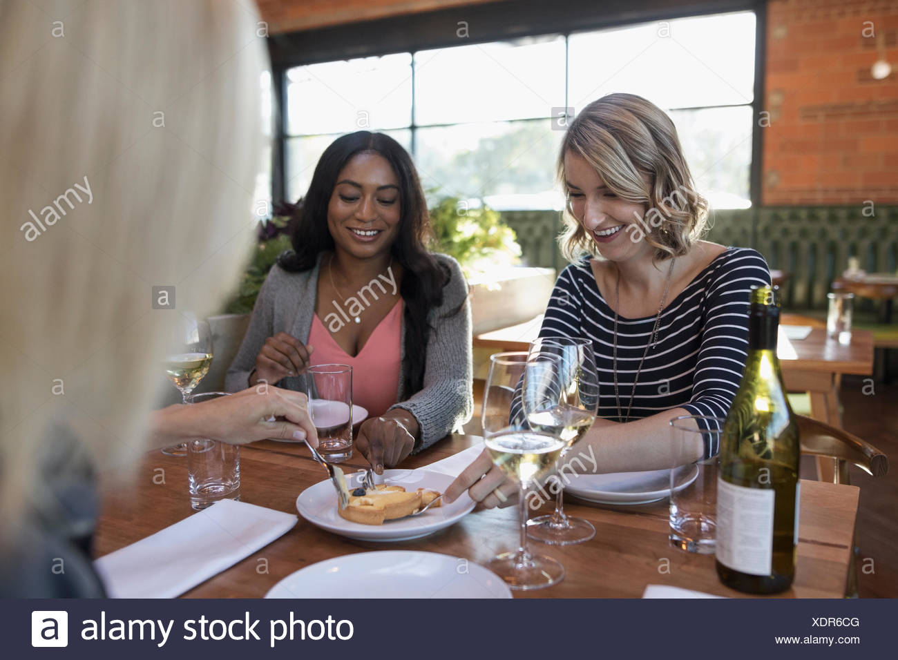 Women friends sharing dessert and drinking white wine, dining at restaurant table - Stock Image