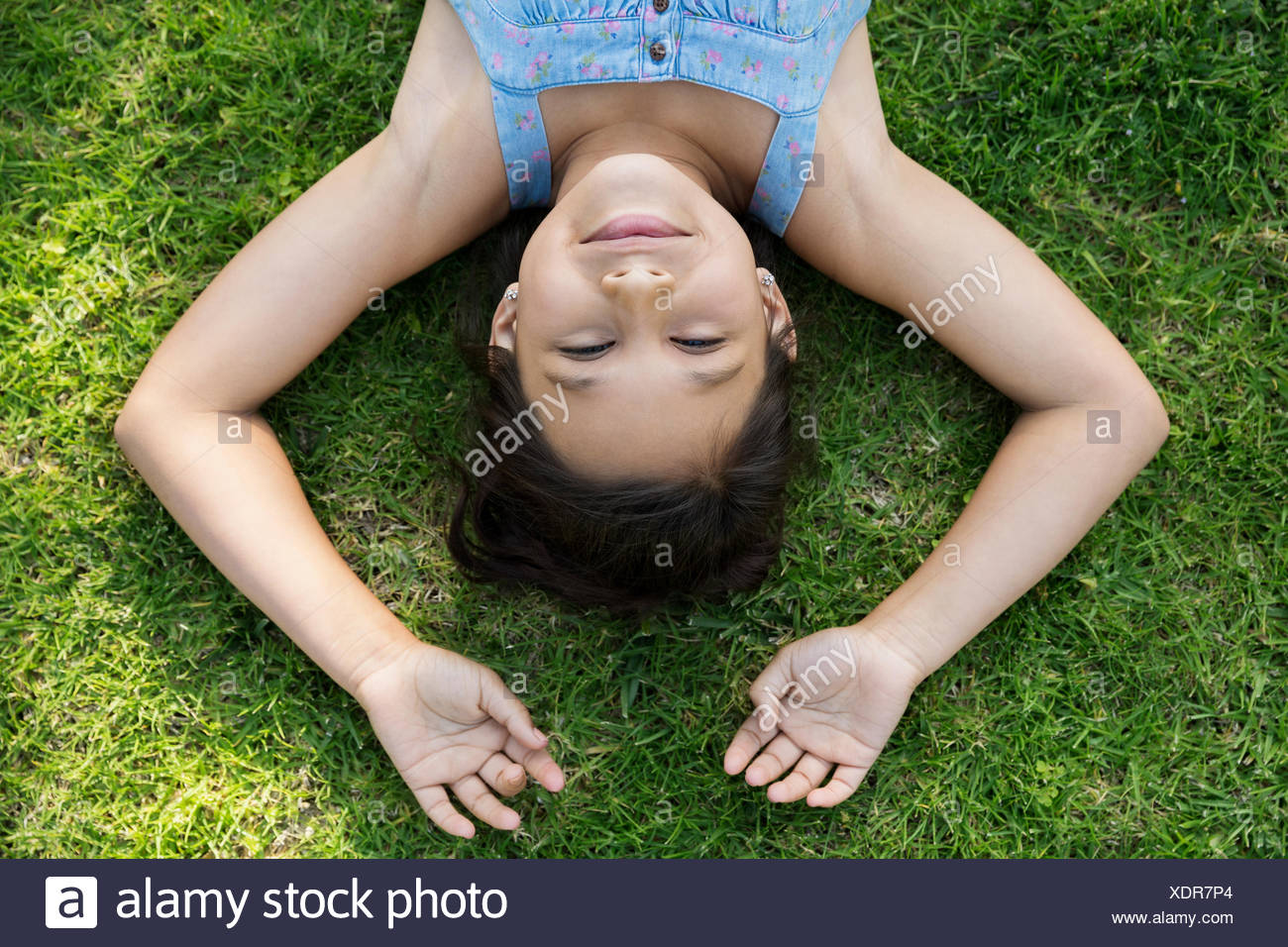 Overhead portrait brunette girl laying in grass - Stock Image