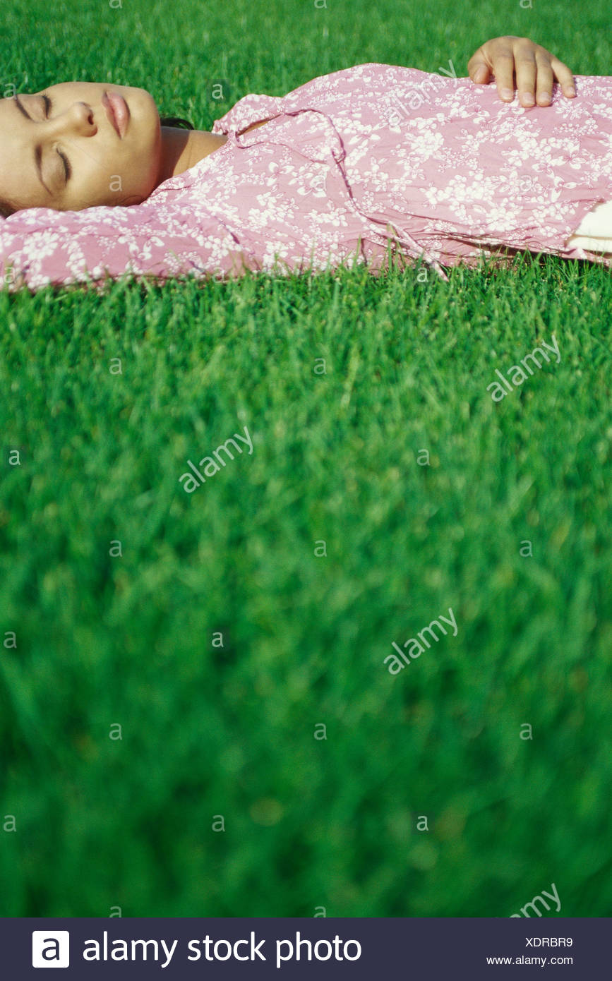 Young woman lying on grass with eyes closed - Stock Image