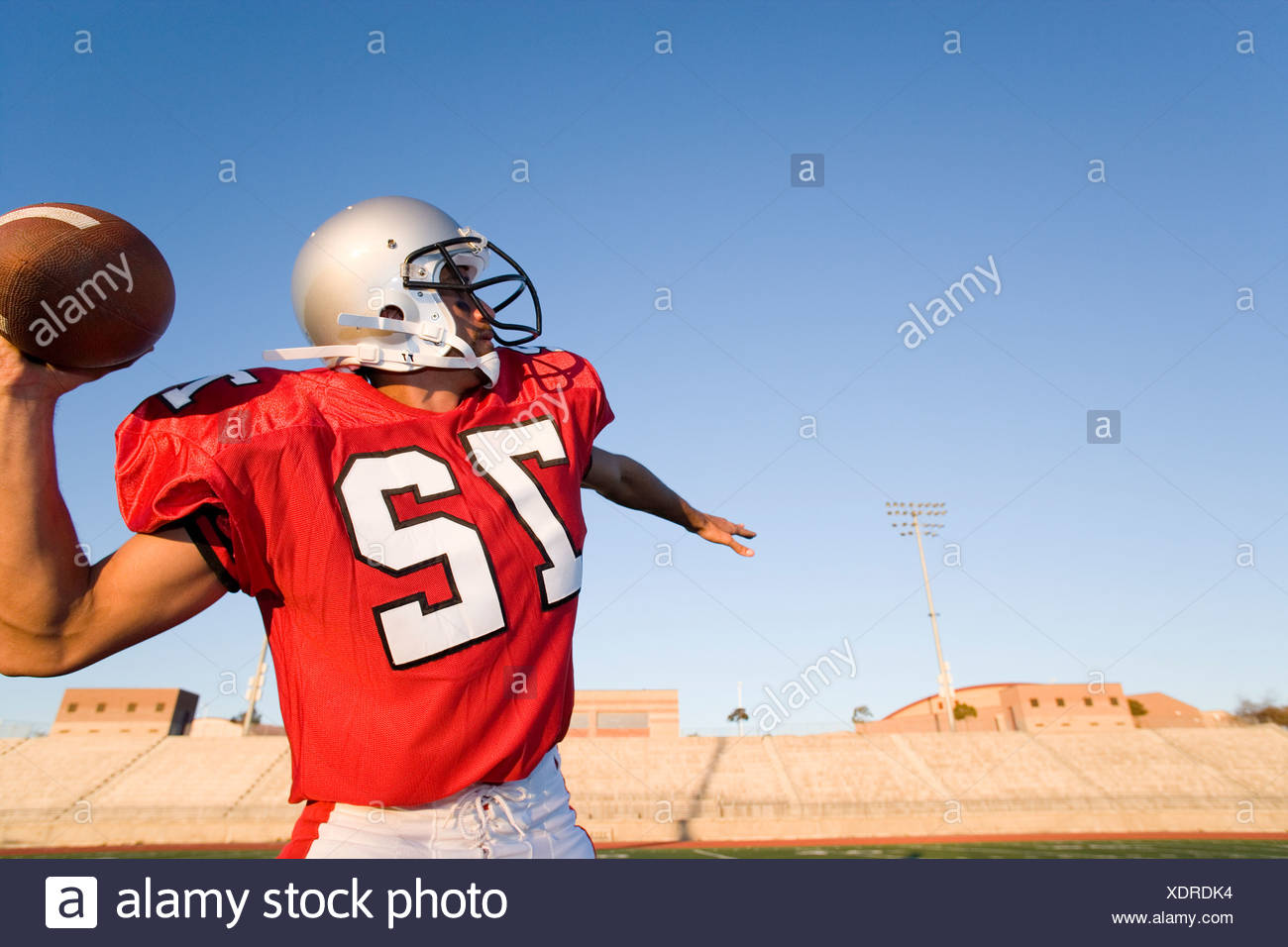 American football quarterback, in red strip, about to throw ball during competitive game, profile - Stock Image