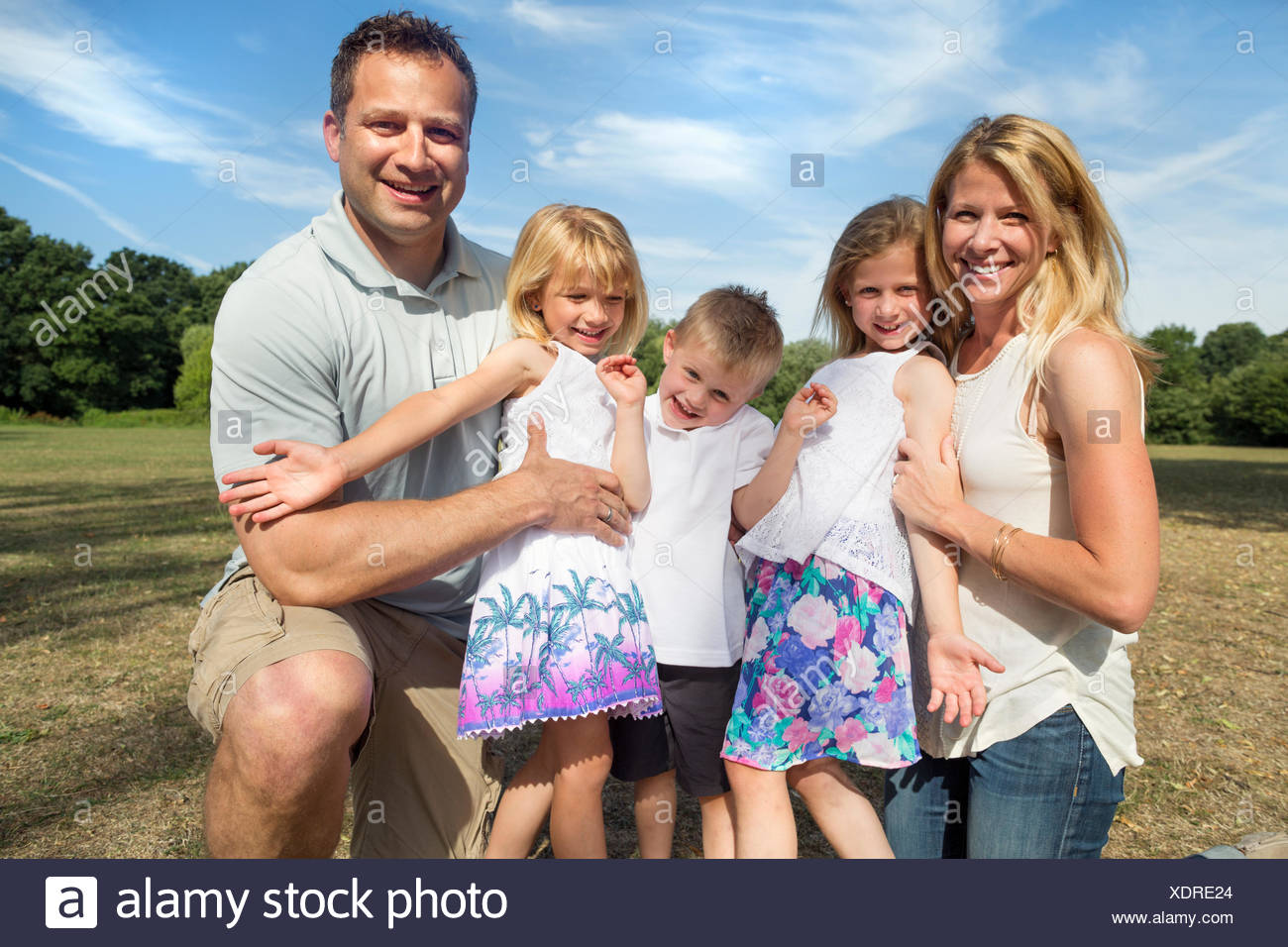 Family with three children in a park, posing for a picture. - Stock Image