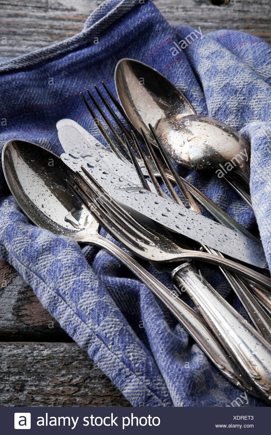Old tarnished silver cutlery with water drops on a tea towel - Stock Image