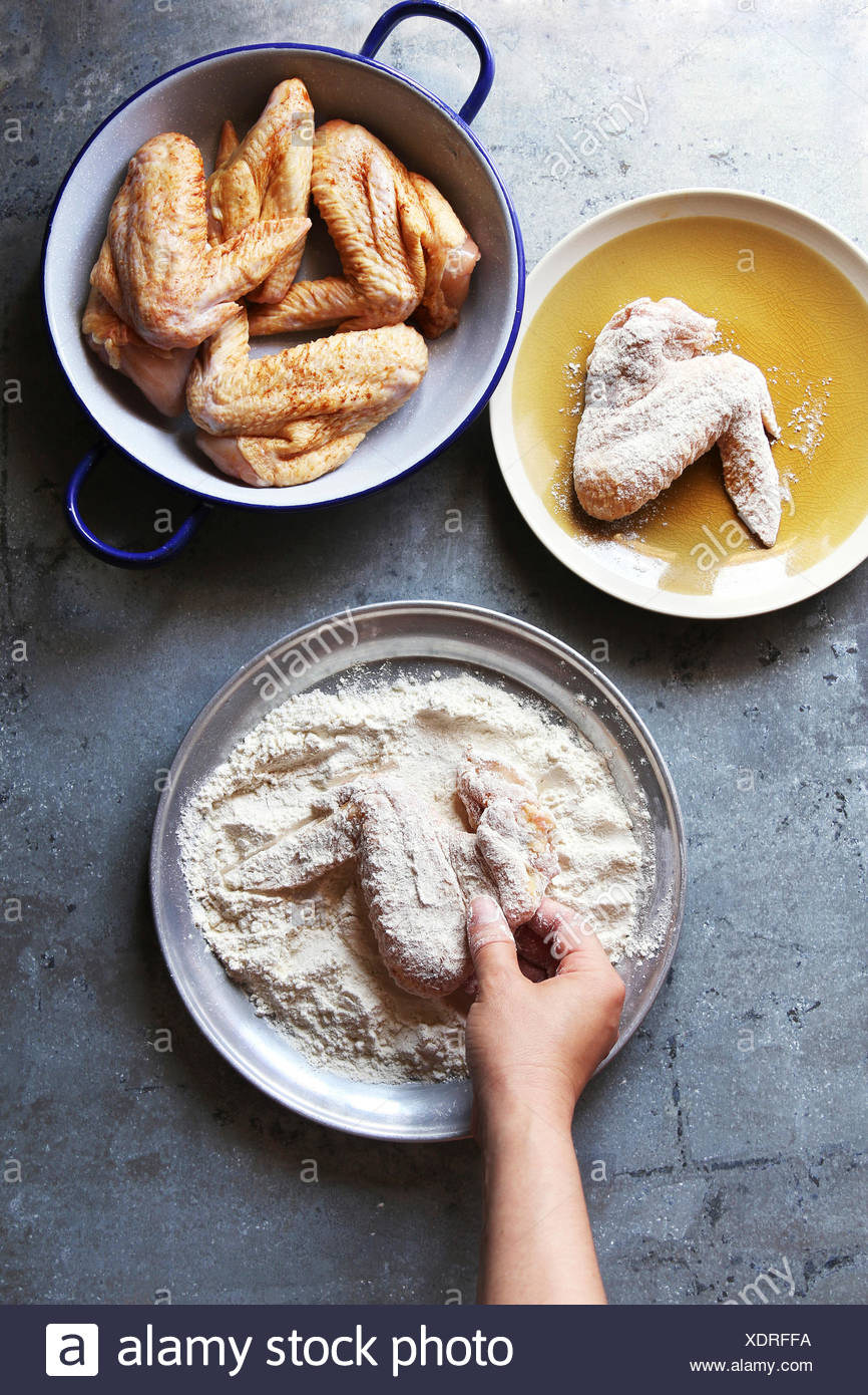 Female hand coating raw chicken wings with flour before frying.Top view - Stock Image
