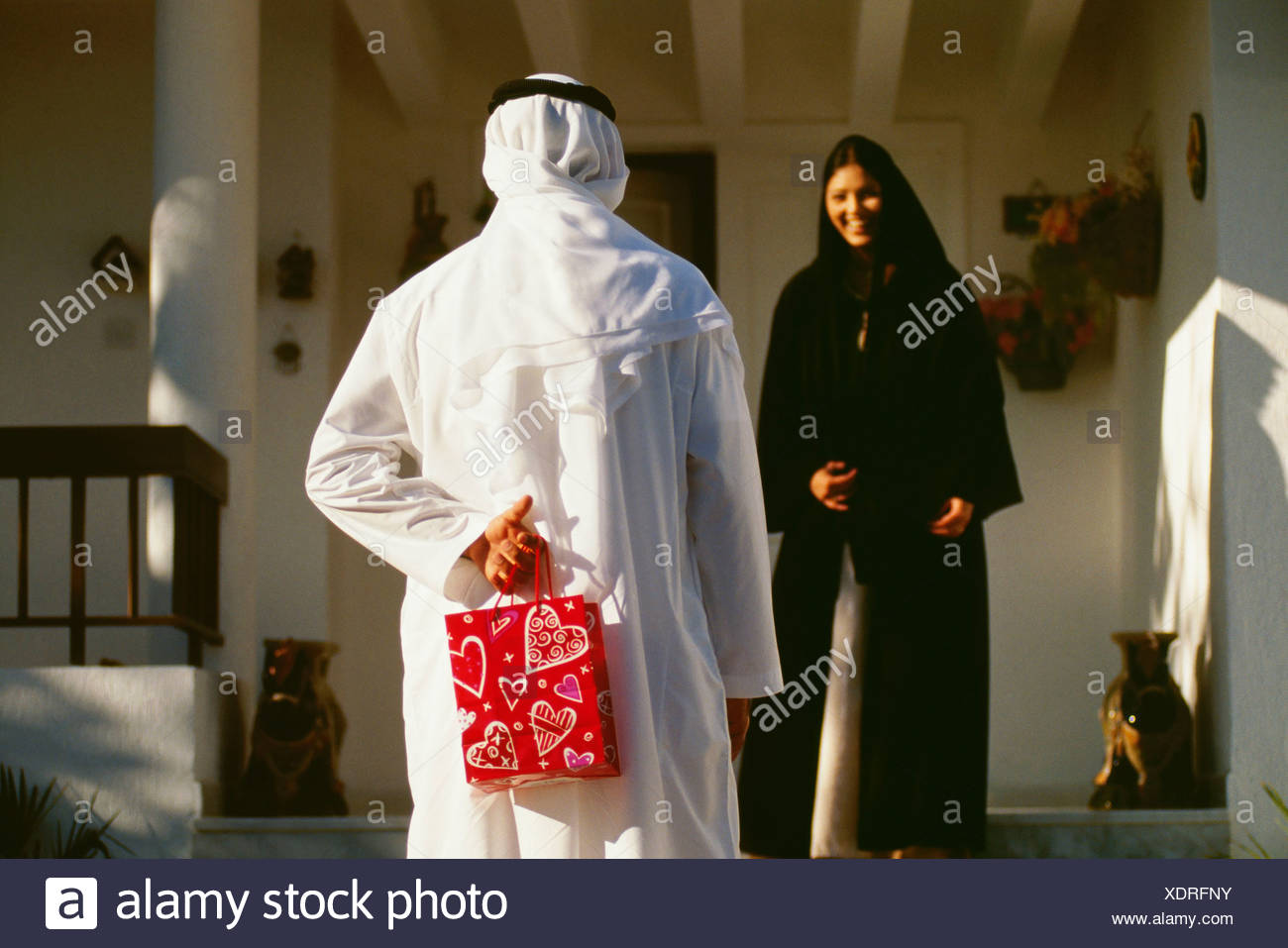 Rear view of a husband hiding a gift from his wife. - Stock Image