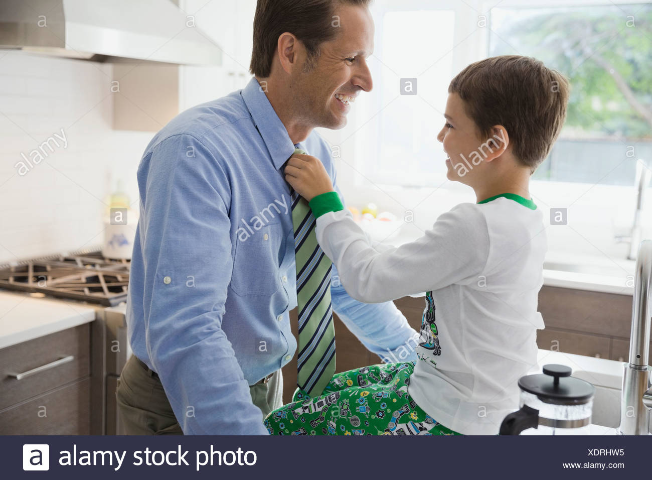 Son adjusting fathers necktie in kitchen - Stock Image