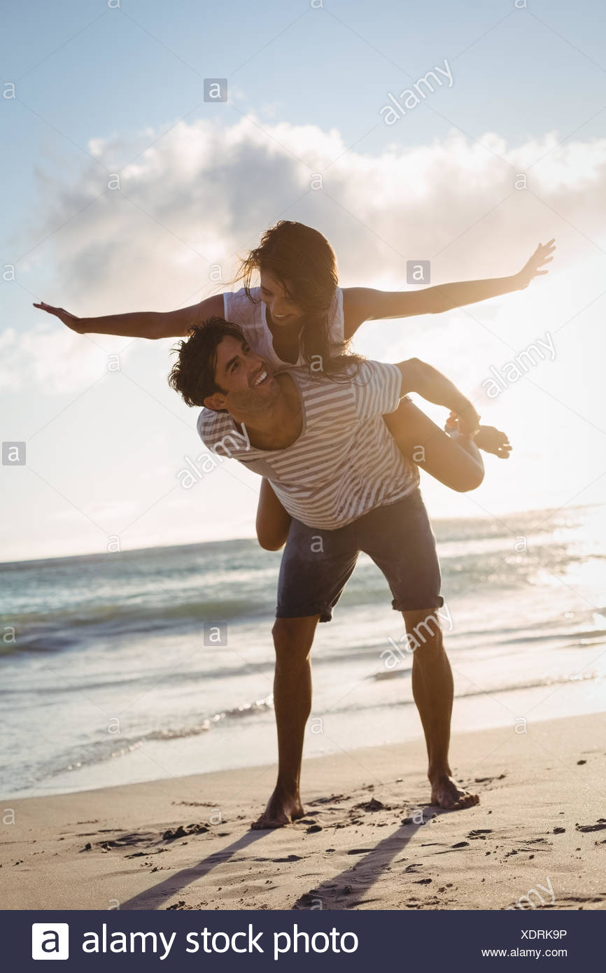 Man giving woman piggyback ride - Stock Image