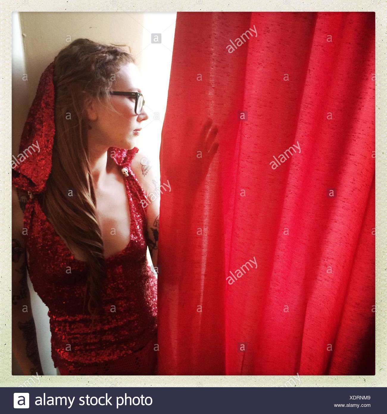 Young Woman Looking Behind Red Curtain - Stock Image