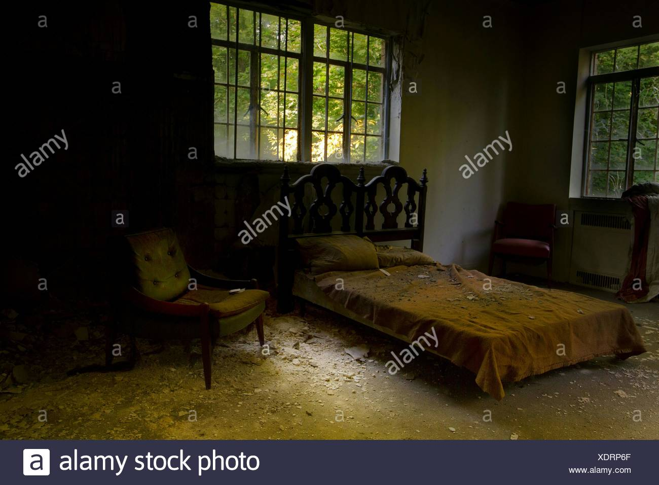 Messy Bed And Chair In Abandoned Room Of Old House - Stock Image