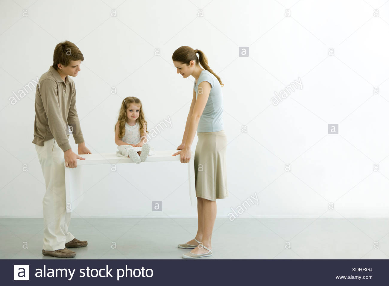Young couple carrying table with daughter sitting on it - Stock Image