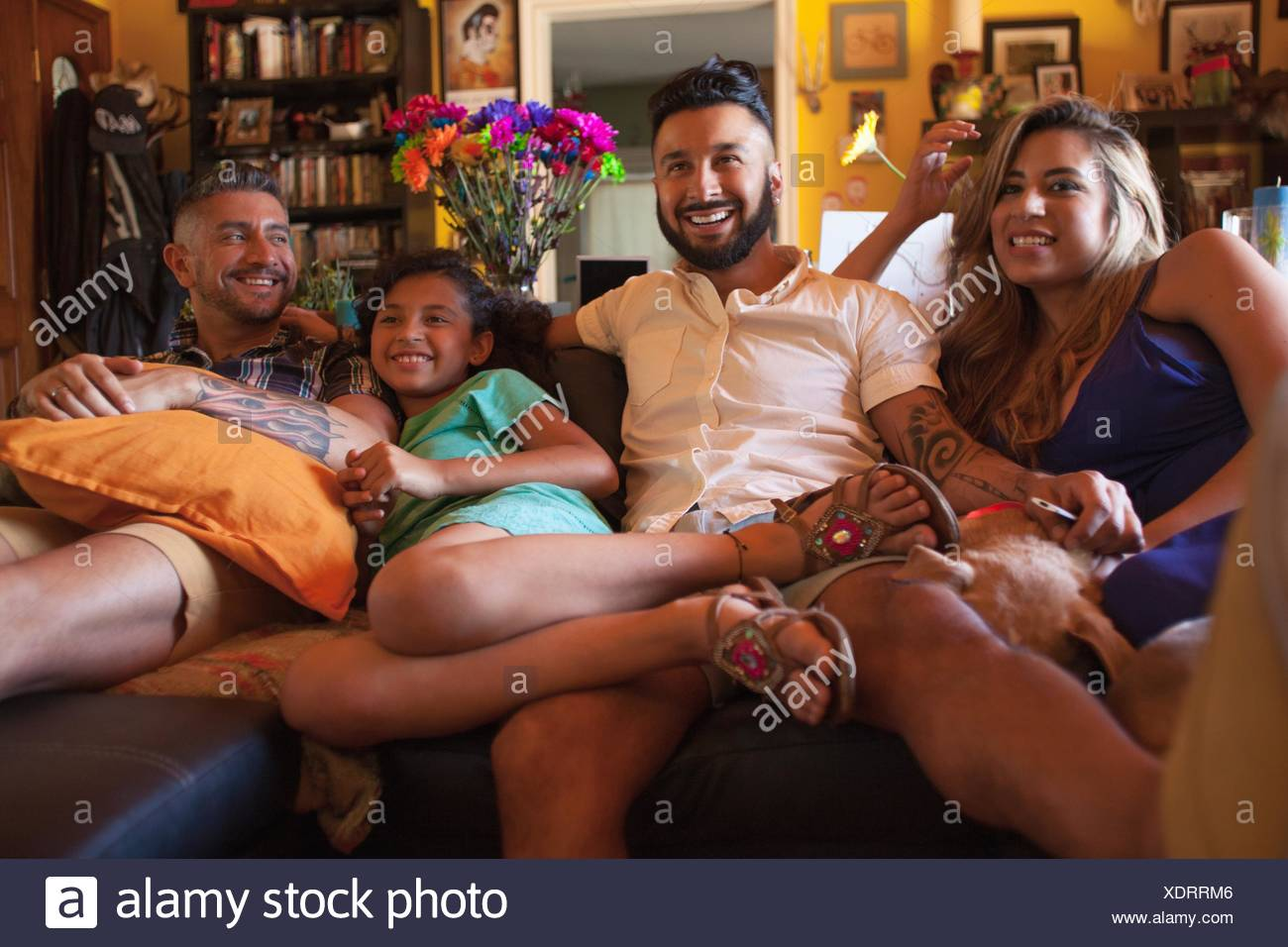 Girl and family watching TV on living room sofa Stock Photo