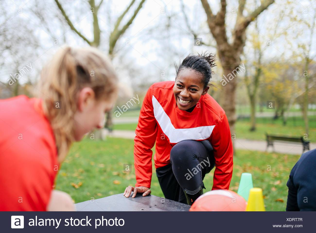 Adult female soccer players preparing to play soccer in park - Stock Image