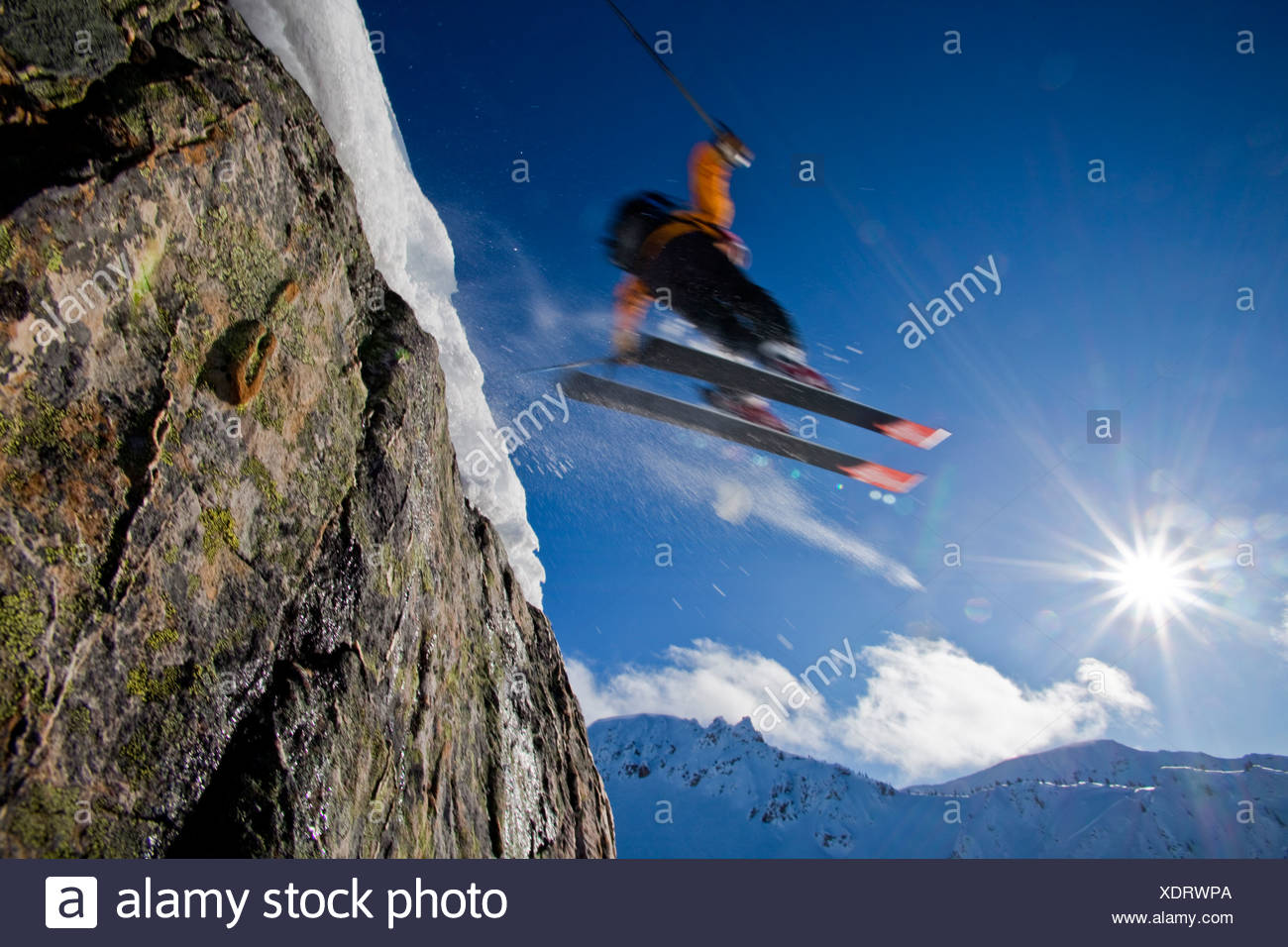 a man backcountry skiing airs off a cliff into the sun, Kicking Horse Backcountry, Golden, British Columbia, Canada - Stock Image