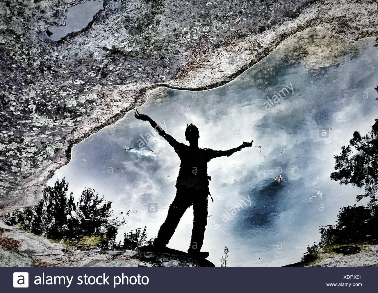 Reflection Of Man On Puddle - Stock Image