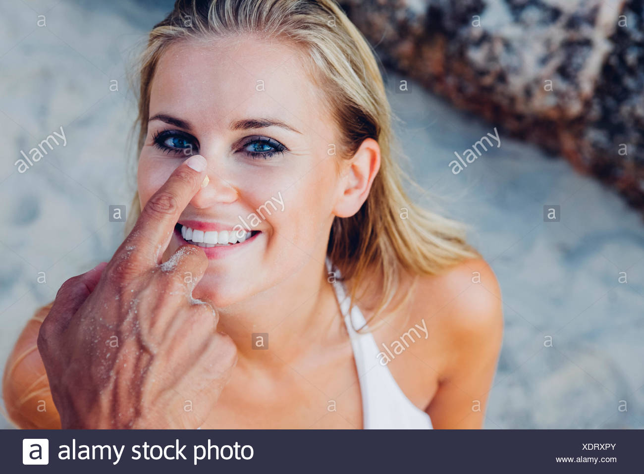 Man's hands applying sunscreen lotion on woman's nose and face at the beach - Stock Image