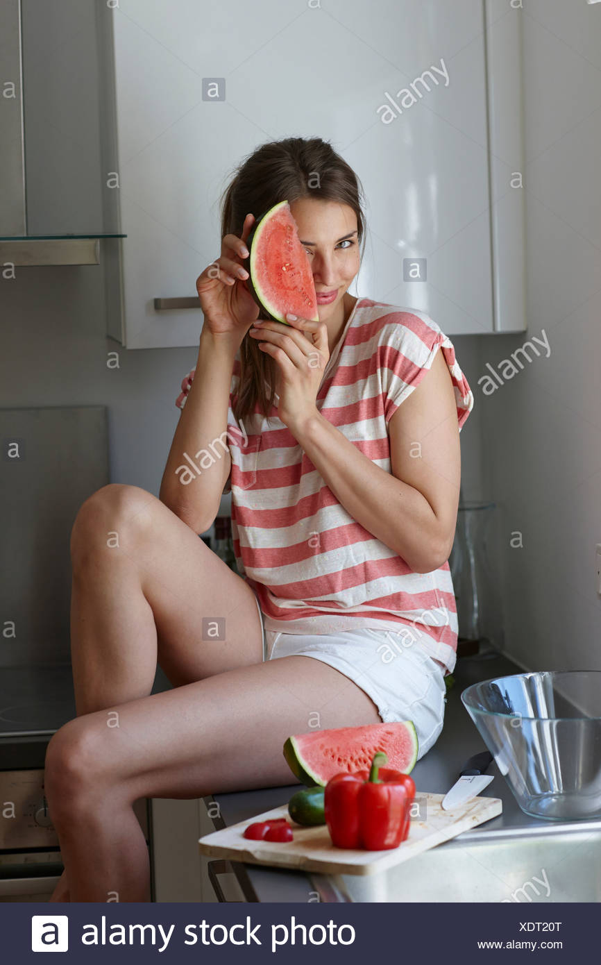Woman covering face with slice of watermelon - Stock Image