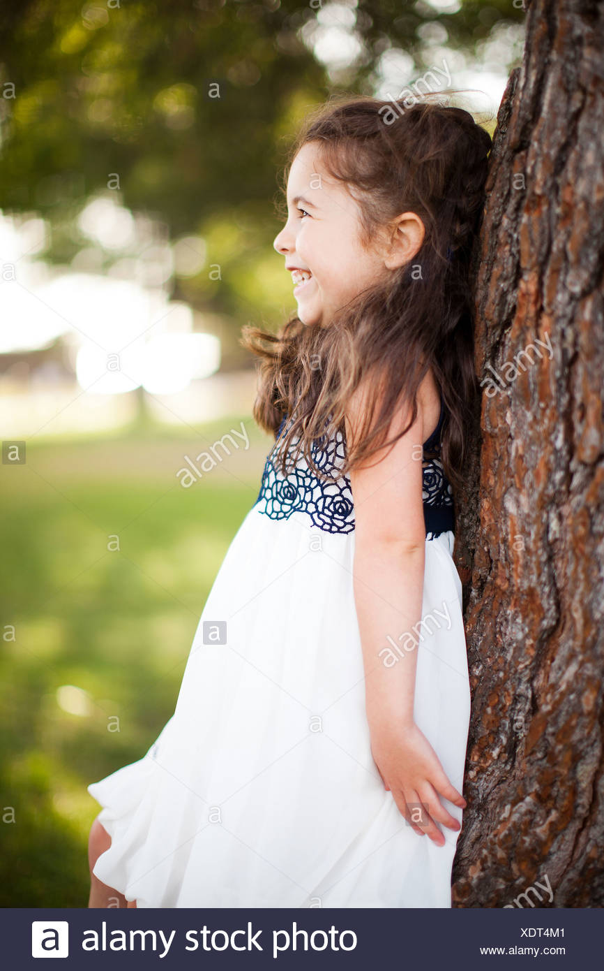 Portrait of girl leaning against tree trunk, smiling - Stock Image