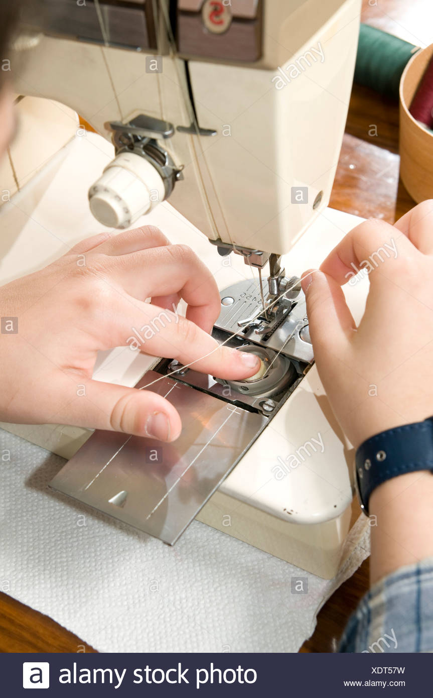 Young female teen of fifteen sewing Threading the bobbin Model release available - Stock Image