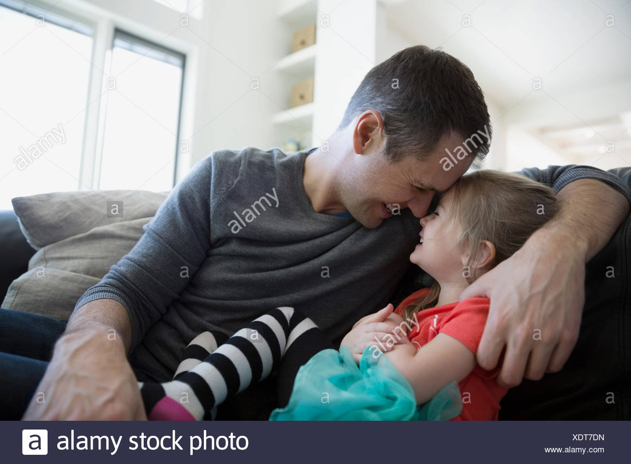 Affectionate father and daughter rubbing noses on sofa - Stock Image