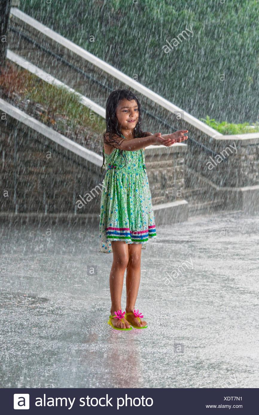 Little girl enjoying in the rain - Stock Image