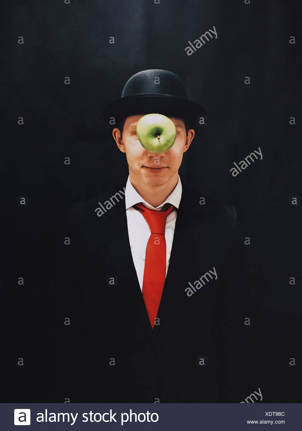 Apple In Mid-Air In Front Of Man With Hat Against Black Background - Stock Image