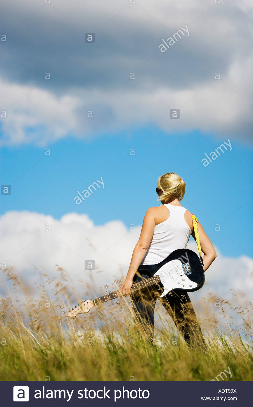 Young woman with electric guitar - Stock Image
