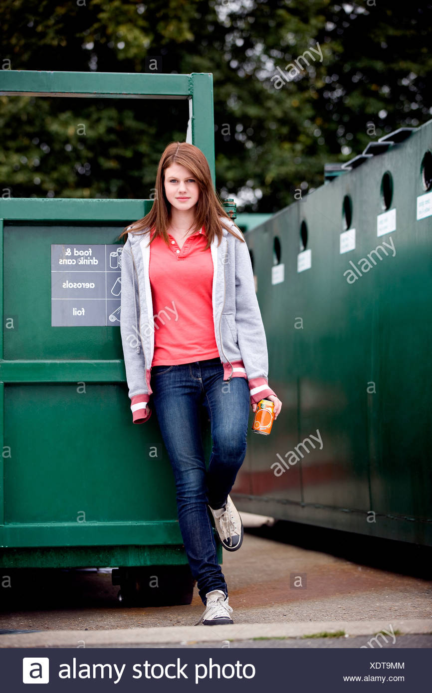 A teenage girl standing next to a recycling container for food and drink cans - Stock Image