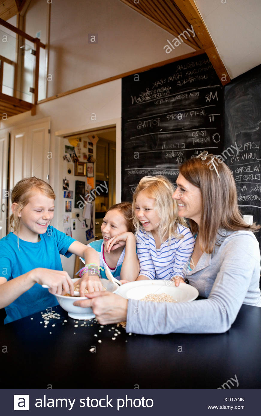 Mother and daughters preparing food together - Stock Image