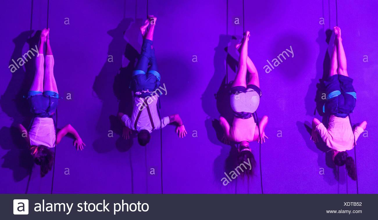 acrobats hanging on a rope by their legs - Stock Image