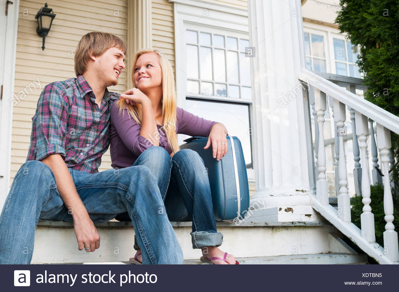 Young couple sitting on step - Stock Image
