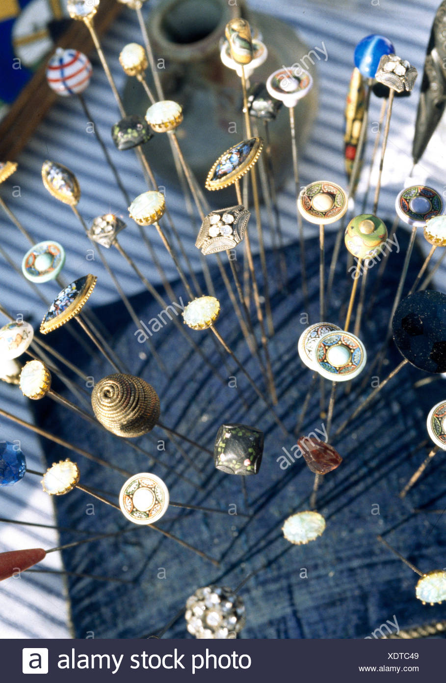 Collection of vintage hat pins displayed on market stall - Stock Image