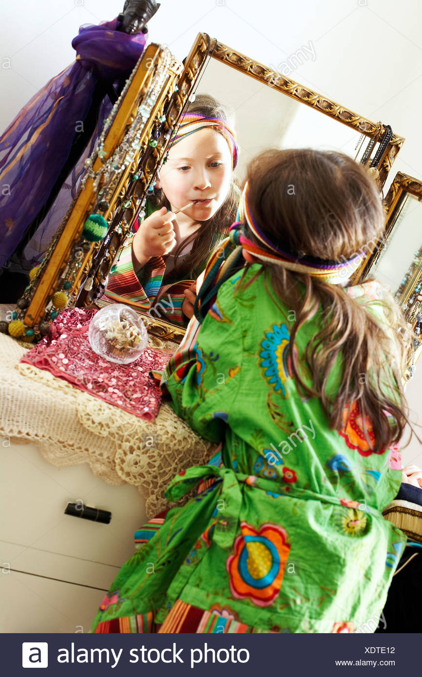 Dressing up. Young girl using a mirror to apply lipstick during a dressing up game. - Stock Image