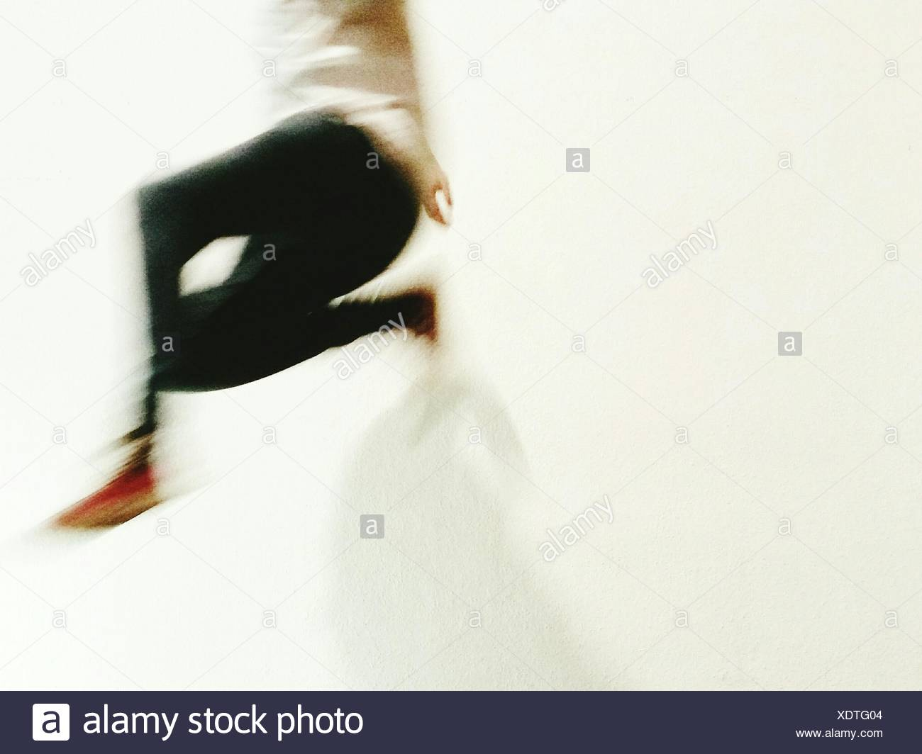 Blurred Image Of Person Jumping Against White Background - Stock Image