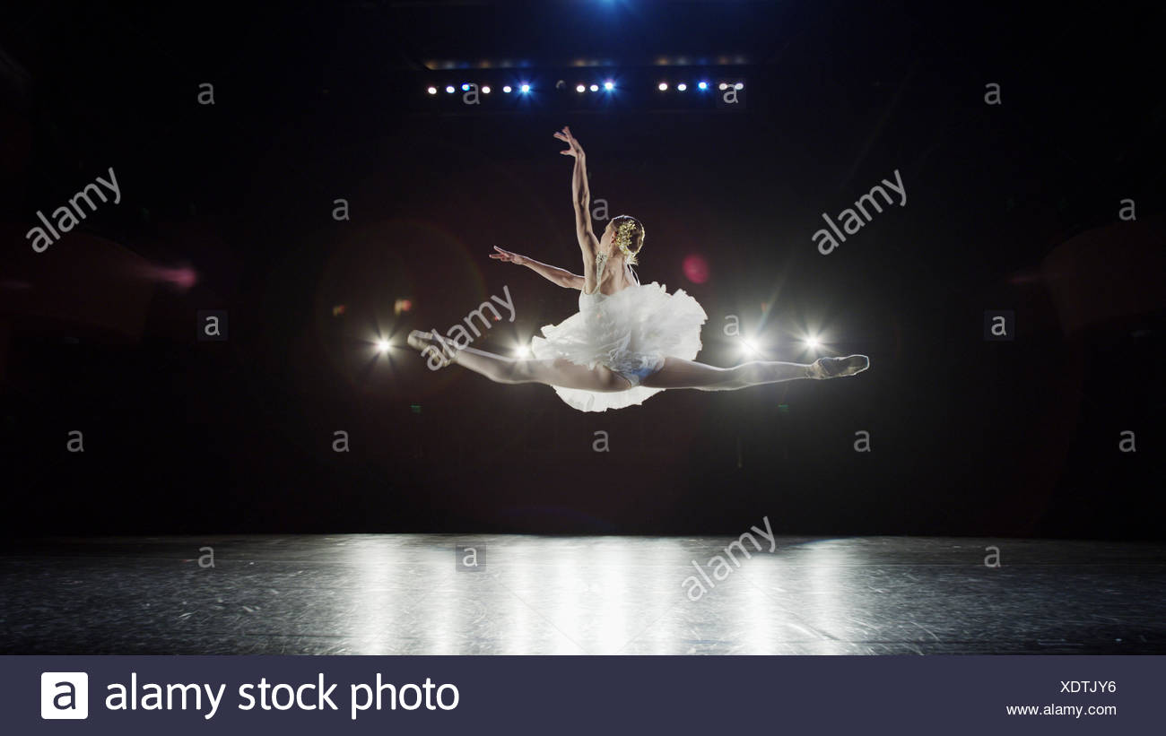 Rear view of serious ballet dancer leaping in costume performing onstage in show - Stock Image