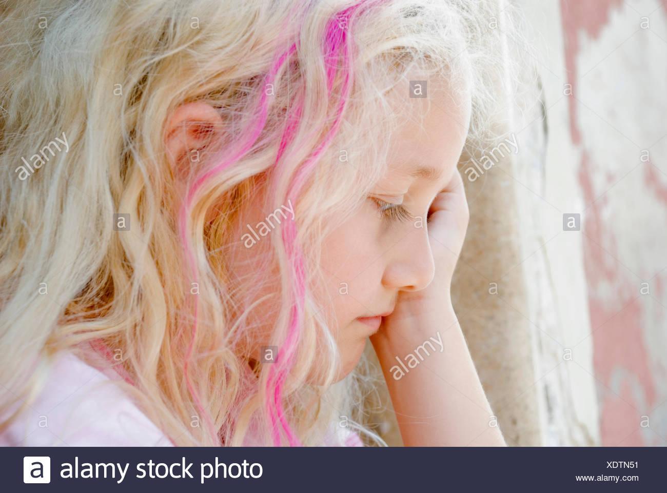 sad girl crouching at a wall Stock Photo