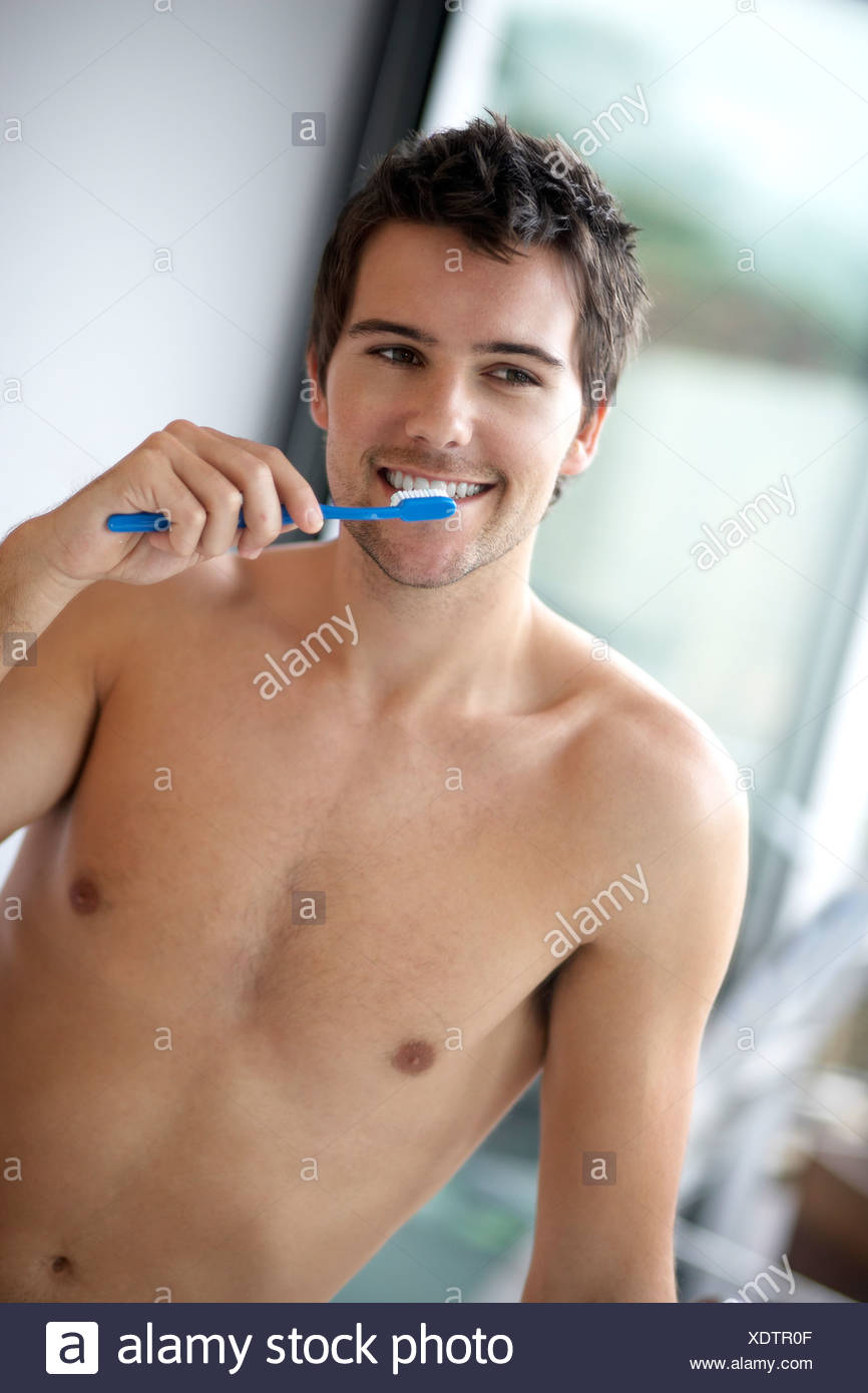 Young man brushing his teeth - Stock Image