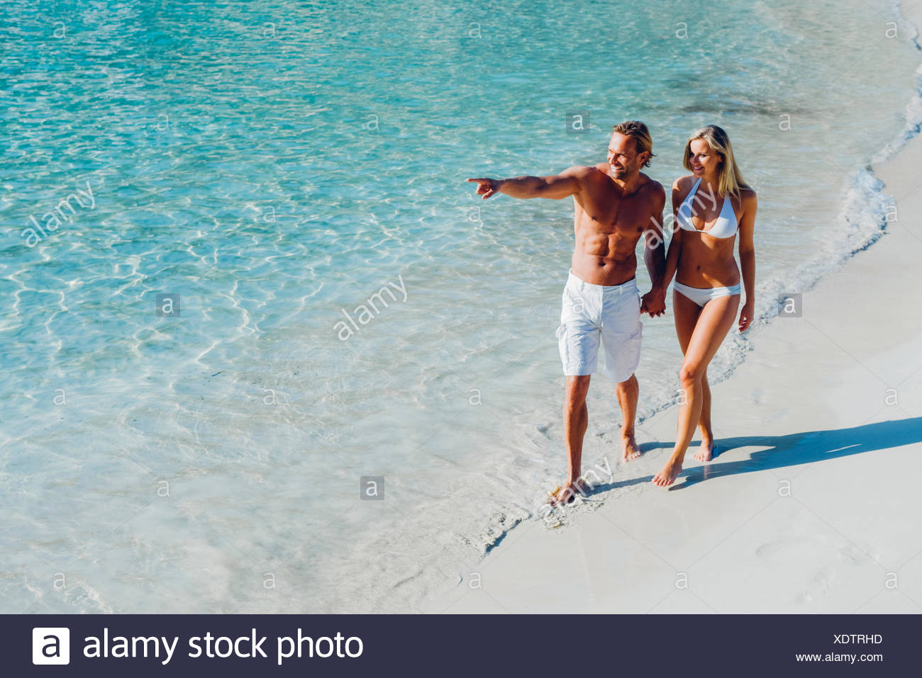 Spain, Majorca, couple walking on the beach with man pointing finger - Stock Image
