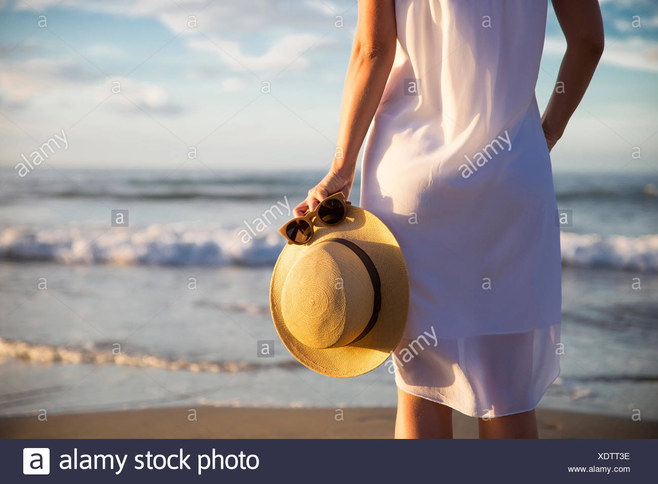 Rear view of woman in white dress standing on beach and holding hat - Stock Image