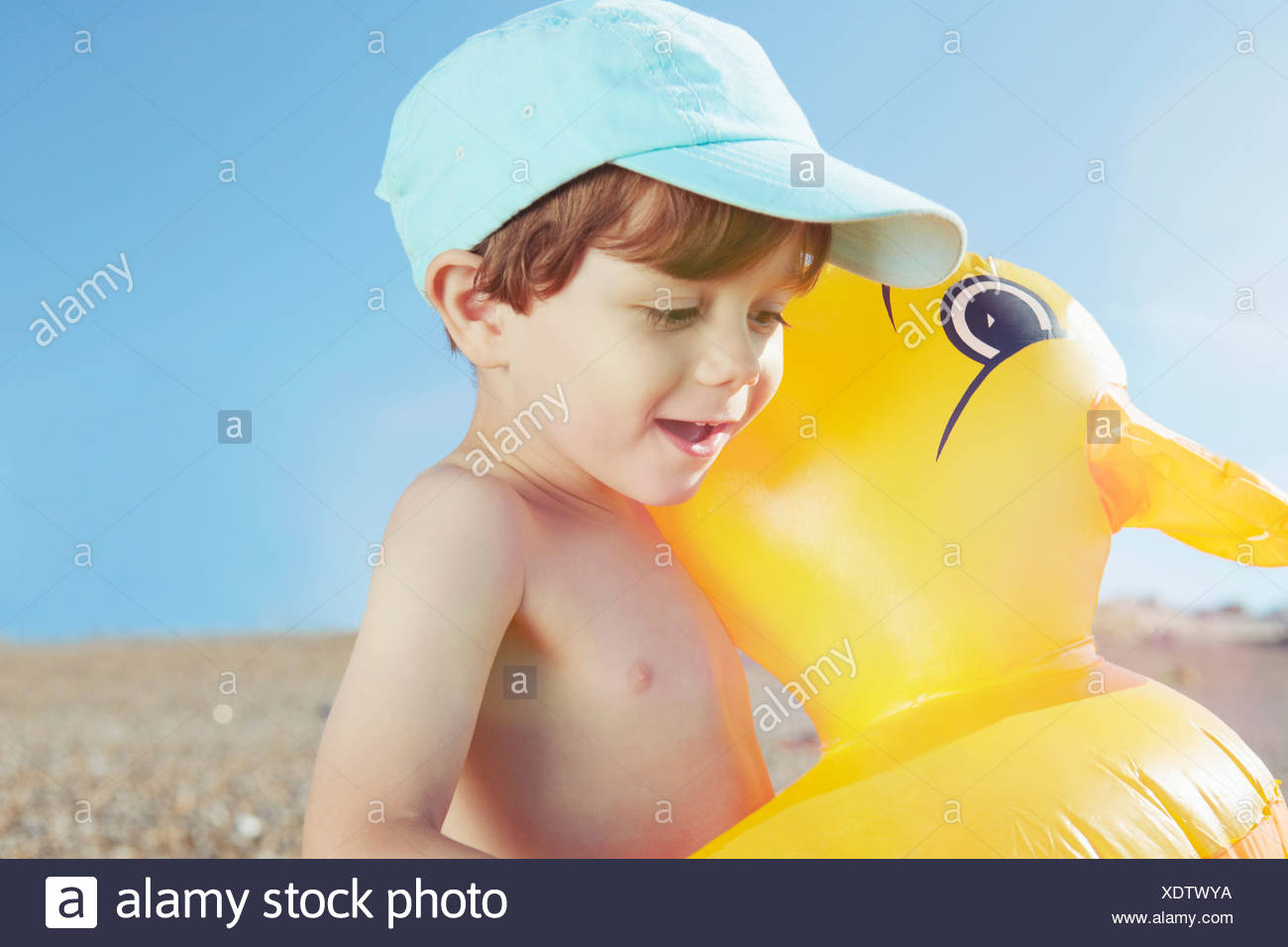 Boy hugging duck shaped float - Stock Image