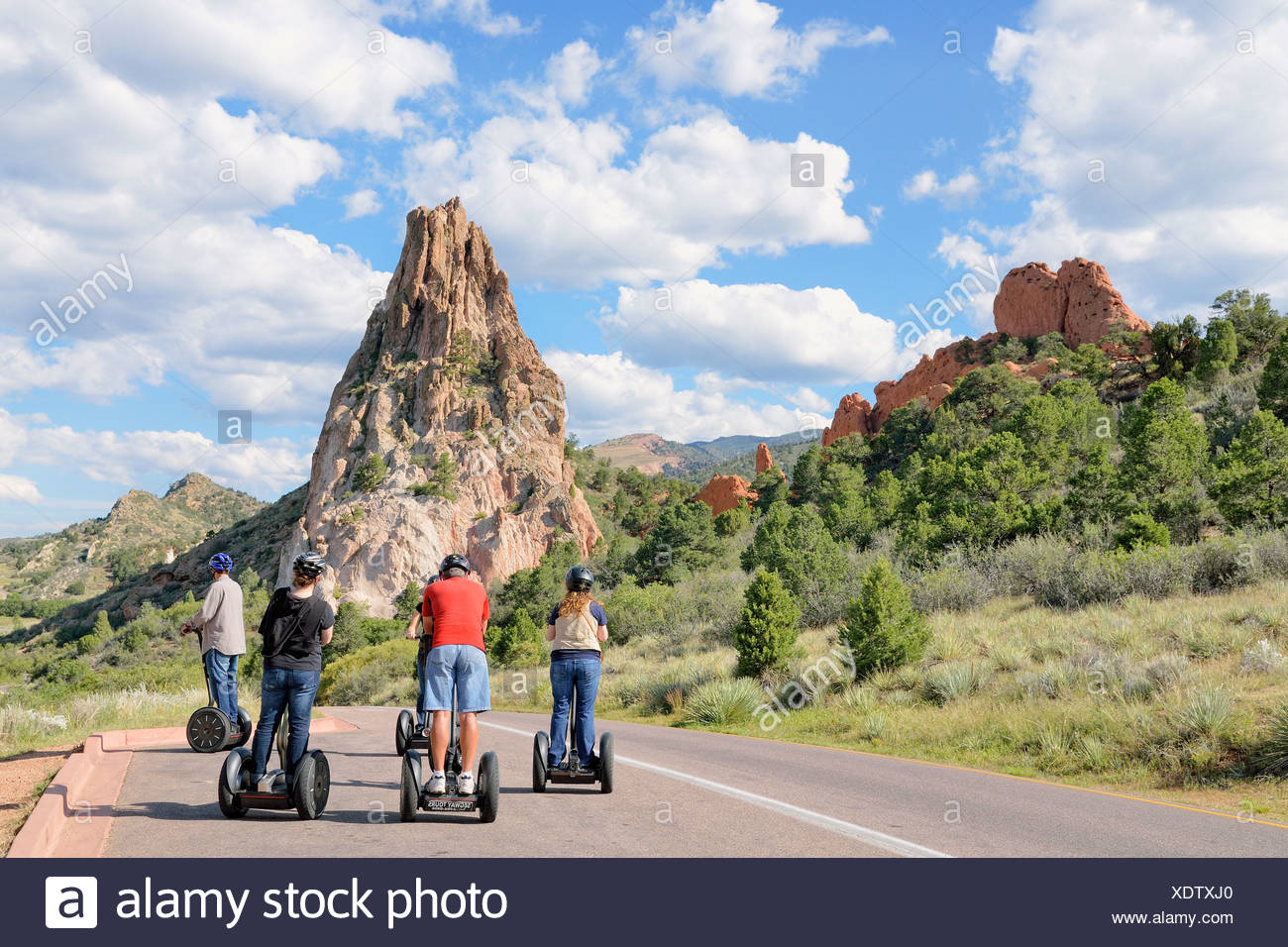 Young people riding Segways in front of Gray Rock or Cathedral Rock, Garden of the Gods, red sandstone rocks, Colorado Springs - Stock Image