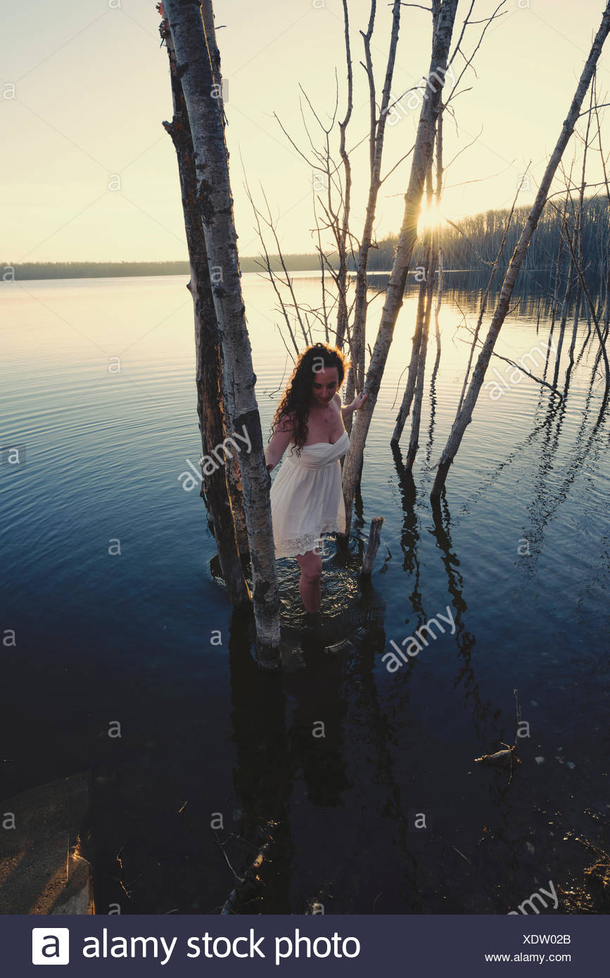 A woman in a white dress or nightdress in shallow water at dusk - Stock Image