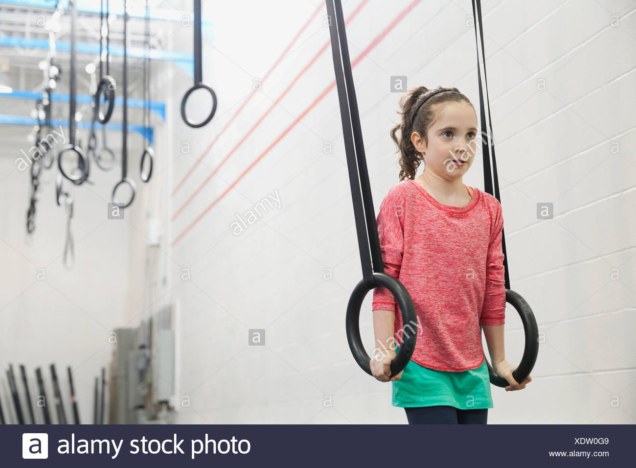 Girl exercising lifts with gymnastic rings - Stock Image