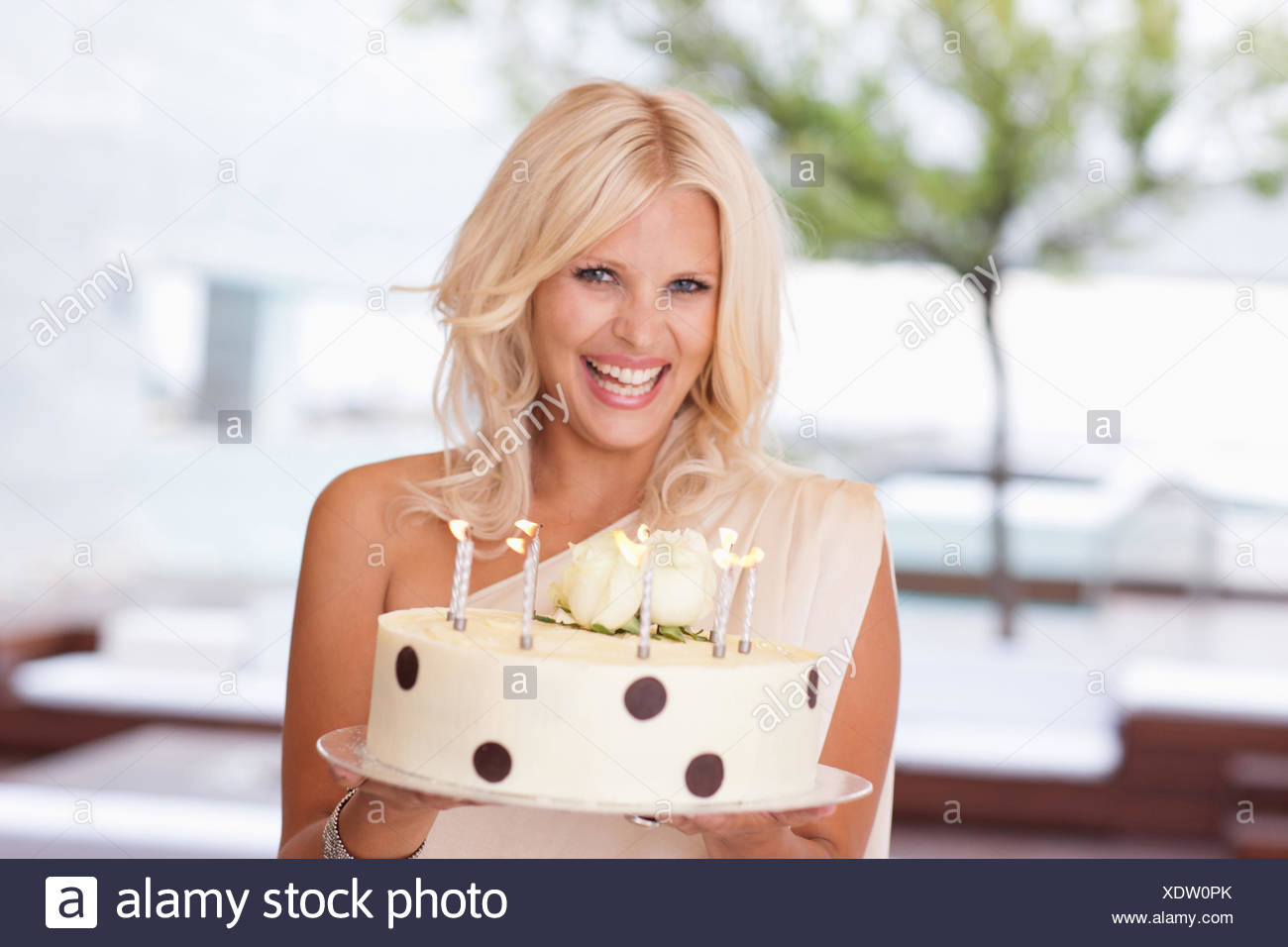 Portrait of woman holding birthday cake - Stock Image
