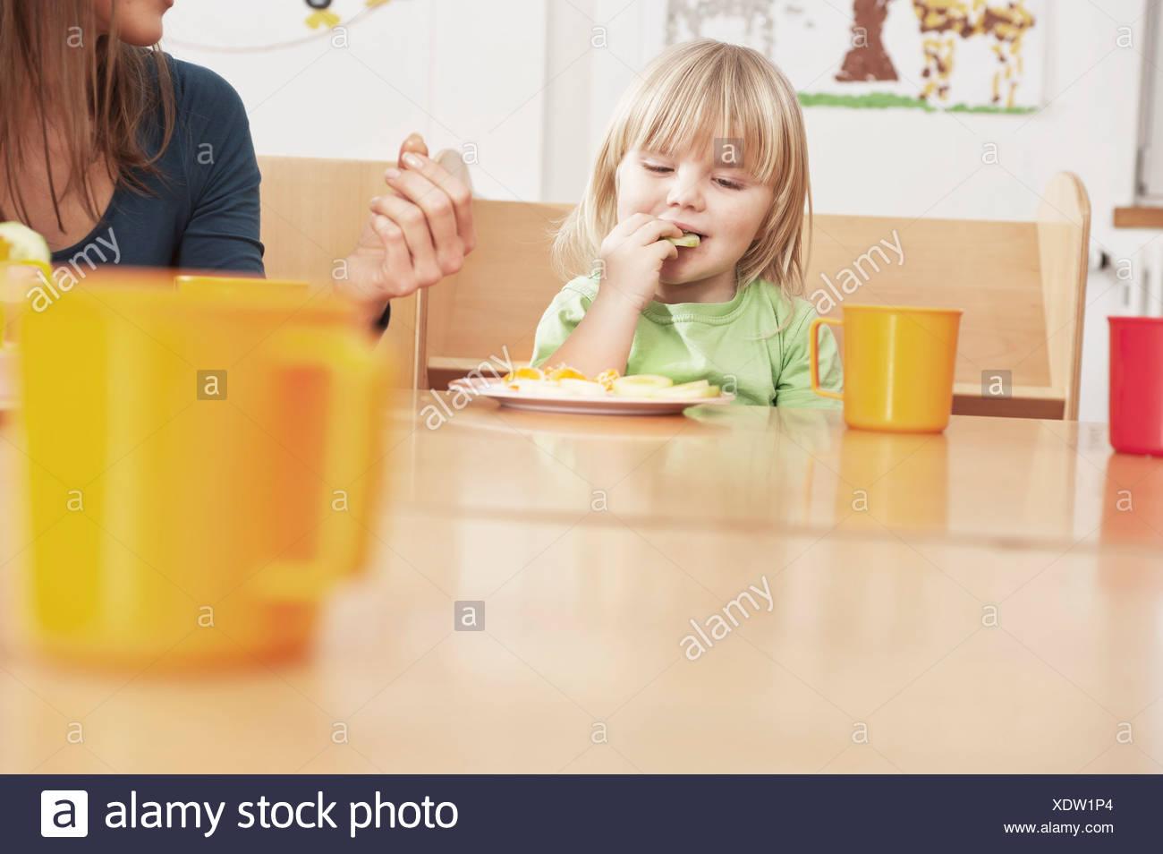 Girl and Female Carer Eating At Table, Kottgeisering, Bavaria, Germany, Europe - Stock Image