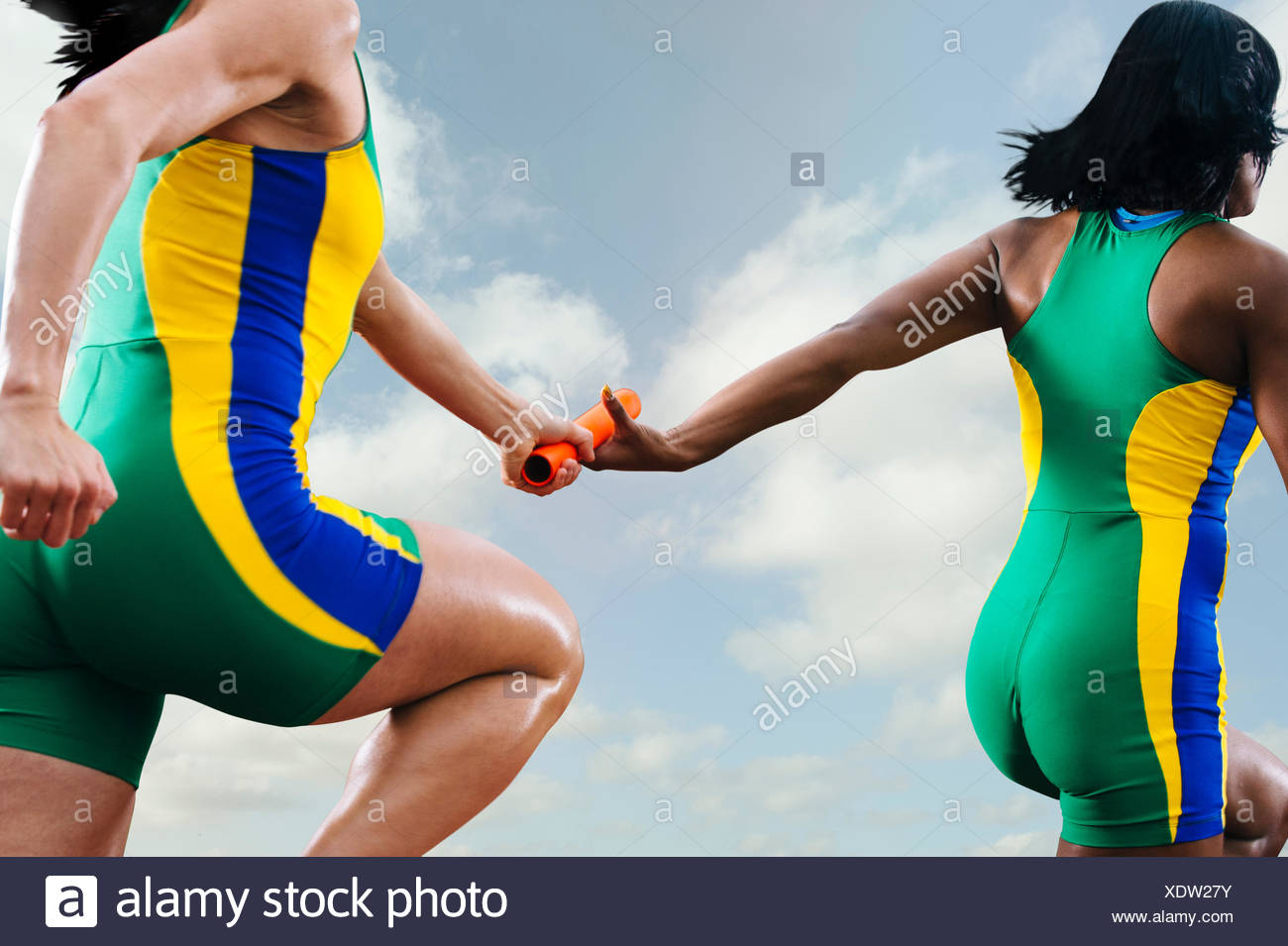 Two female relay athletes exchanging baton whilst running - Stock Image